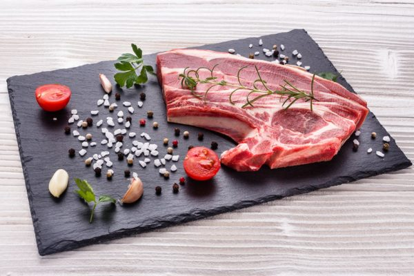 fresh lamb meat on a textured stone plate